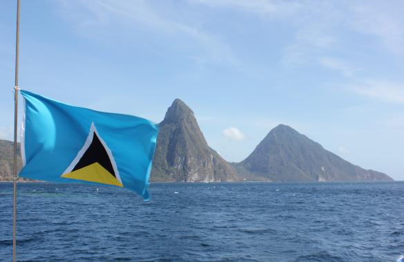 Saint Lucias flagga med bergstopparna i bakgrunden