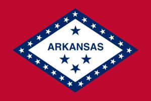 Röd flagga med vit fyrkant i mitten med texten Arkansas i blått och en blå kant som innehåller vita stjärnor