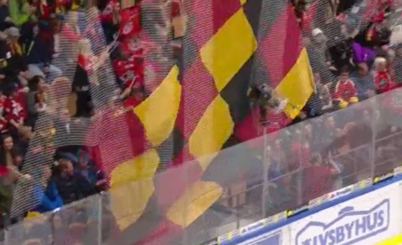 Toyne springer längs sargen med en stor flagga.
